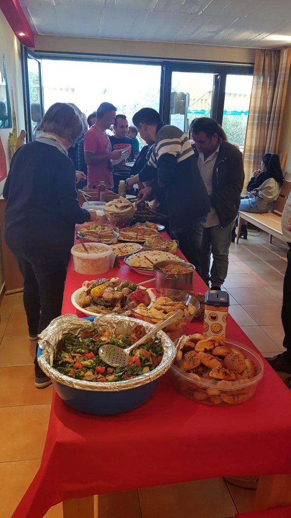 Es ist ein Tisch mit verschiedenen Speisen zu sehen und Frauen und Männer, die sich dran bedienen