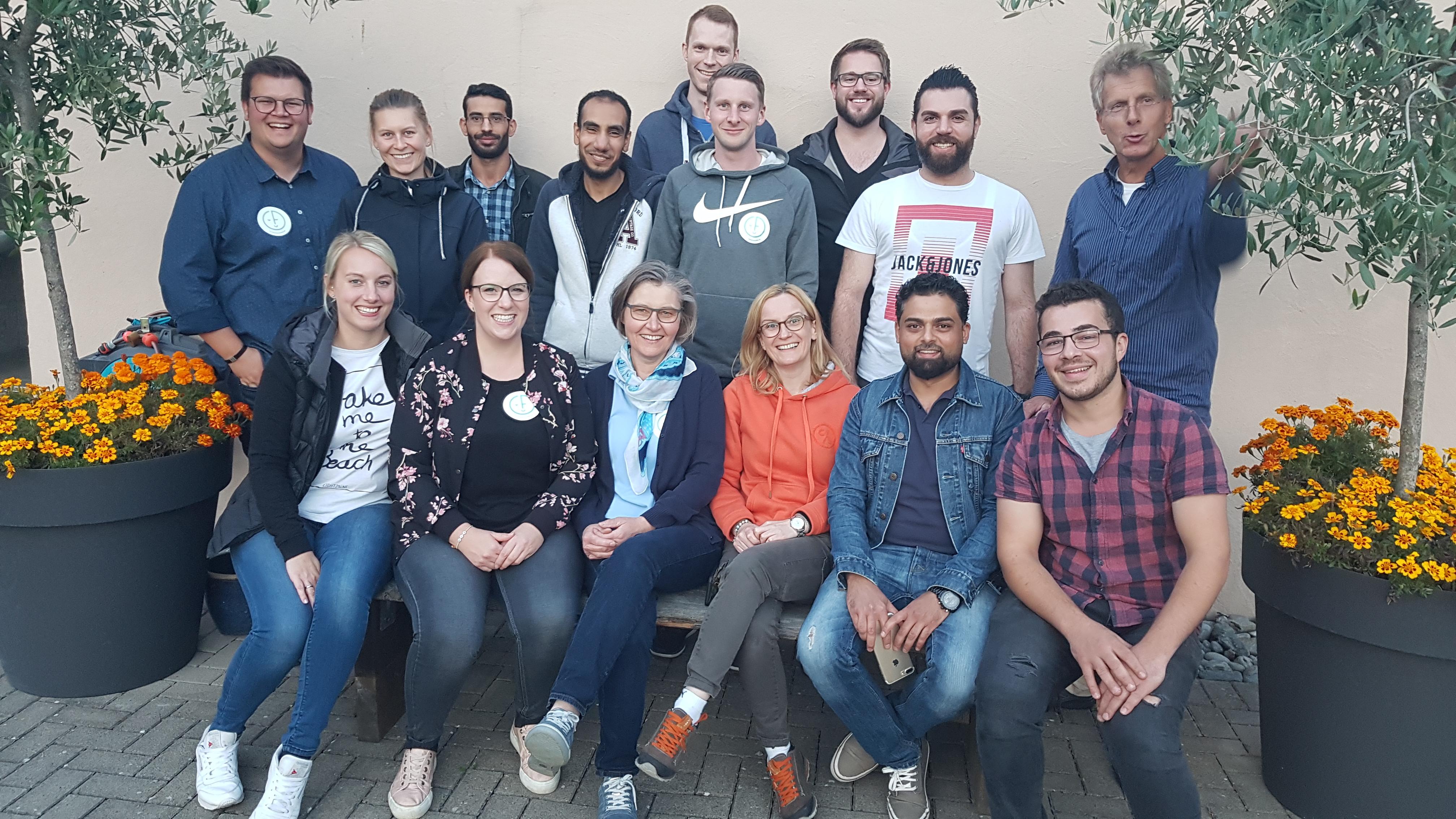 Auf dem Bild sieht man eine Gruppe von Männern und Frauen die für ein Gruppenfoto posieren