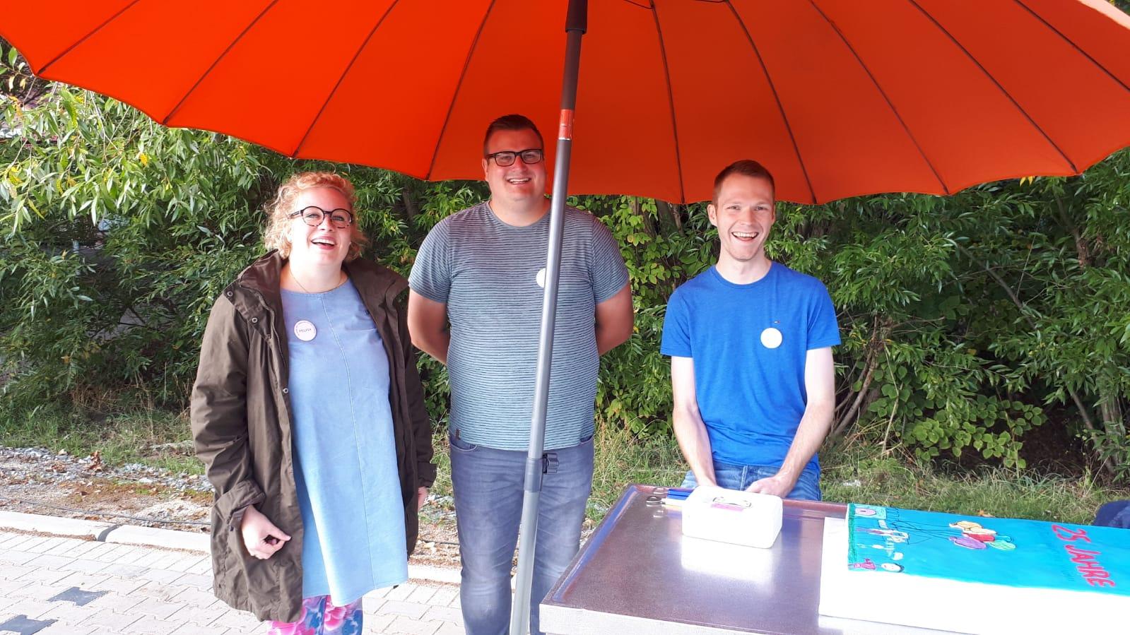 Das Bild zeigt drei lachende Personen hinter einer Theke und unter einem Sonnenschirm
