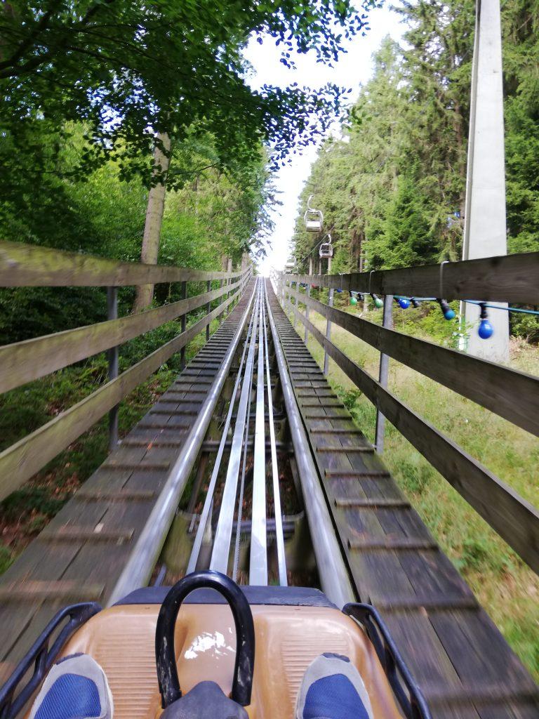 Auf dem Bild sind zwei Füße zu sehen, die in einem Wagen eine Holzachterbahn hinauf fahren.